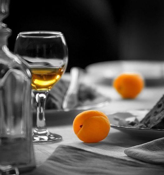 Бокал и абрикос ы на столе