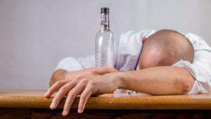 Un om doarme cu o sticlă