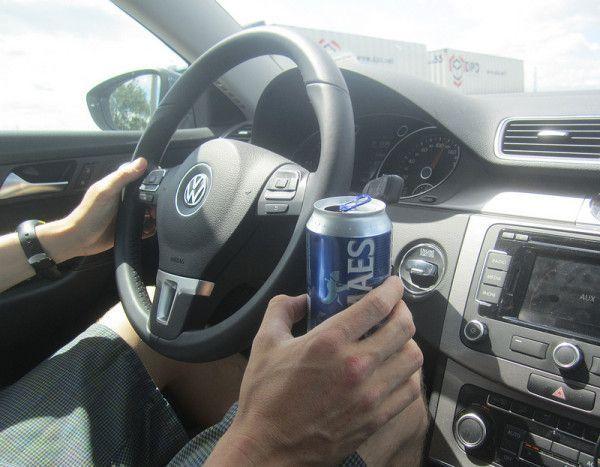 Водитель за рулем с банкой пива