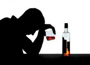 Мужчина держит стакан с алкоголем в руке