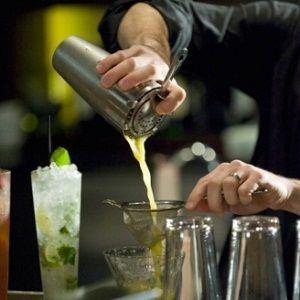 бармен наливает коктейль из шейкера